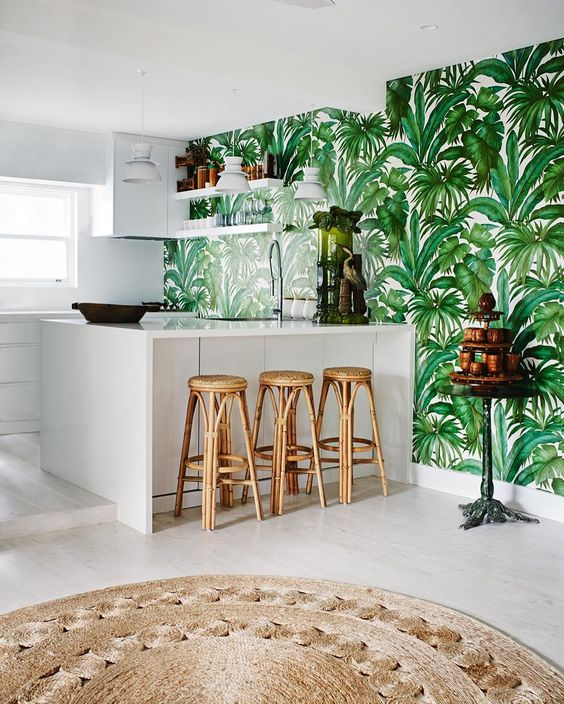 a white tropical kitchen with a tropical leaf print wall, rattan stools, a jute rug feels contemporary and boho