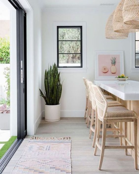 a white tropical kitchen with rattan stools, wicker pendant lamps plus a tropical plant in a pot