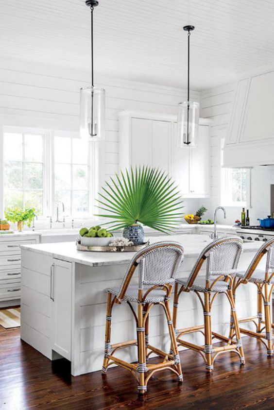 a white tropical kitchen with tropical plants, rattan chairs with blue upholstery and with a contemporary feel