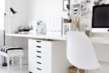 an eclectic black and white home office with white furniture, a black lamp, frames for artworks and a stool with a striped seat