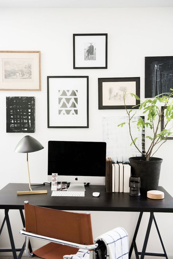 an elegant Scandinavian home office with a blakc trestle desk, a leather chair and a black and white gallery wall