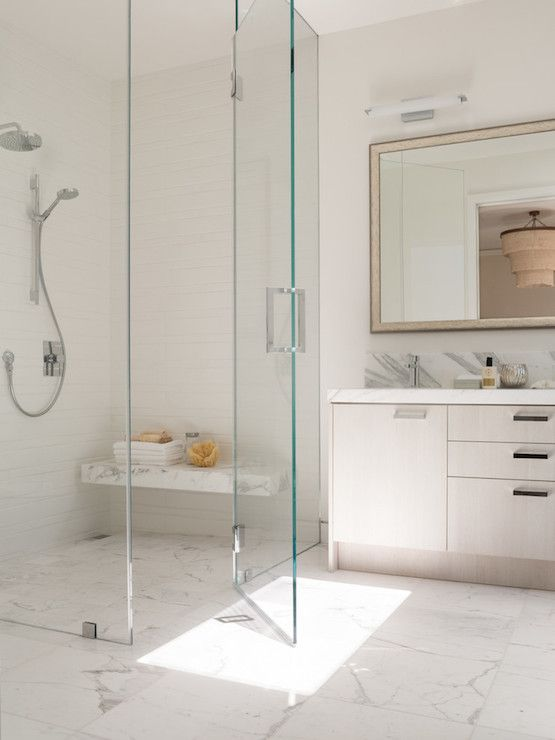 an ethereal shower space with a marble tile floor and a floating bench that matches plus seamless glass doors