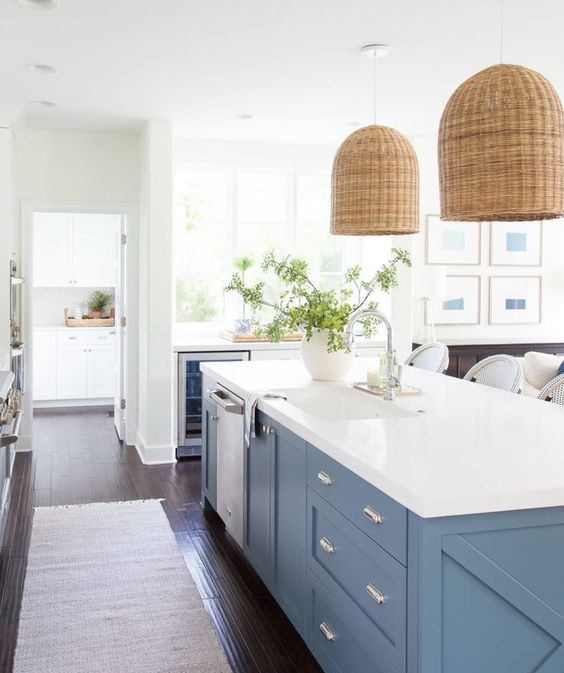 elegant pblue cabinets with a pure white countertop and wicker lamps over them make up a chic look