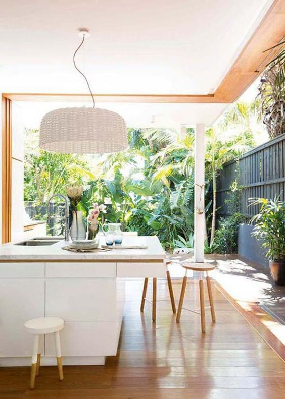 sleek white kitchen island, a white wicker lampshade, wooden stools and a tropical garden, to which the kitchen is opened