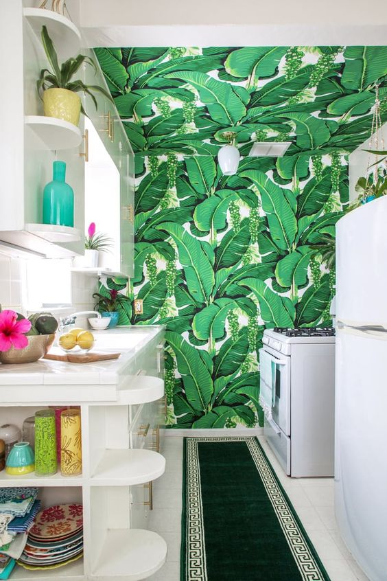 sleek wite cabinets with a banana leaf print taking over the whole space and an emerald rug