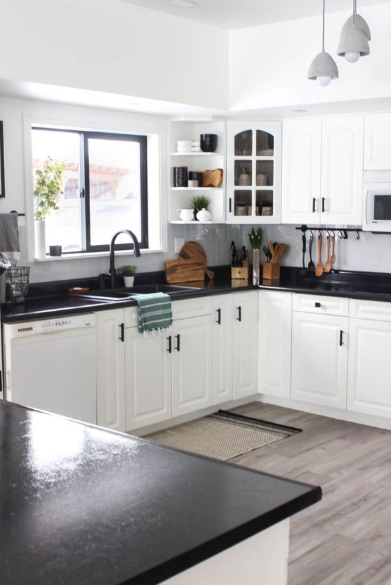 stylish white kitchen cabinets accented with dark stained countertops and black hardware for a bold look