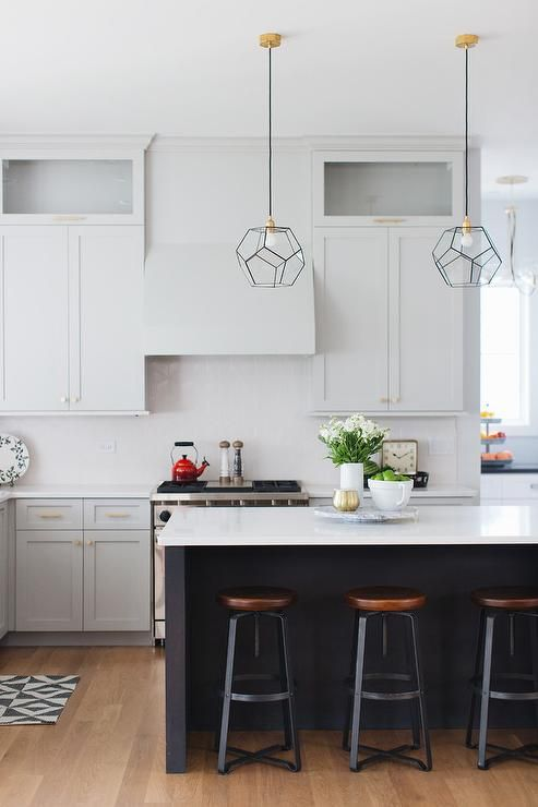 the black kitchen island features a white countertop, the same as on the cabinets to tie them up