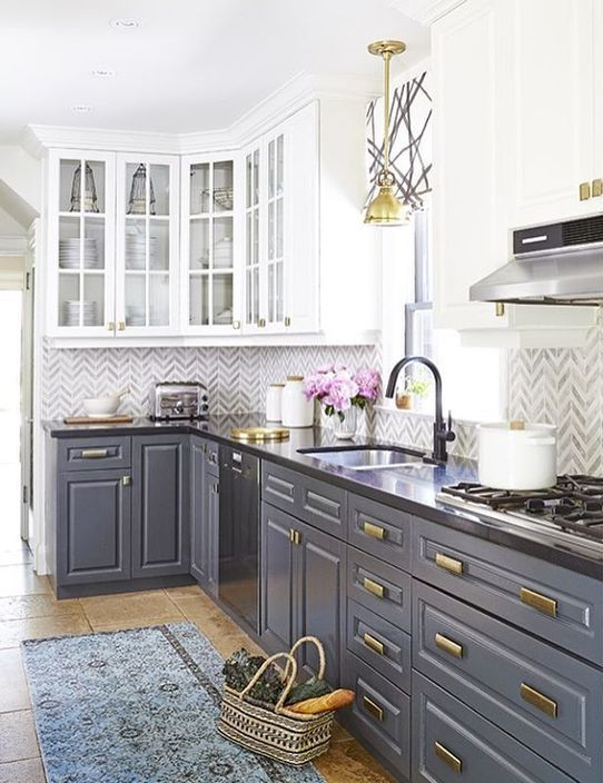 this grey and white kitchen with dark countertops features two trends in one - two colors and contrasting countertops