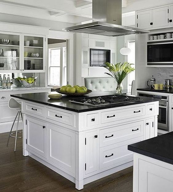 vintage-inspired white cabinets and a large kitchen island in the center with black countertops and black hardware