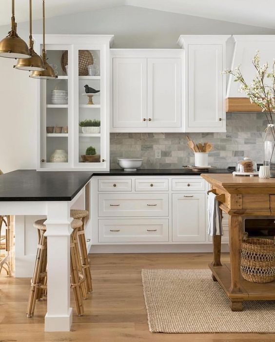 vintage-inspired white cabinets with black countertops and a grey marble tile backsplash for a cozy farmhouse kitchen