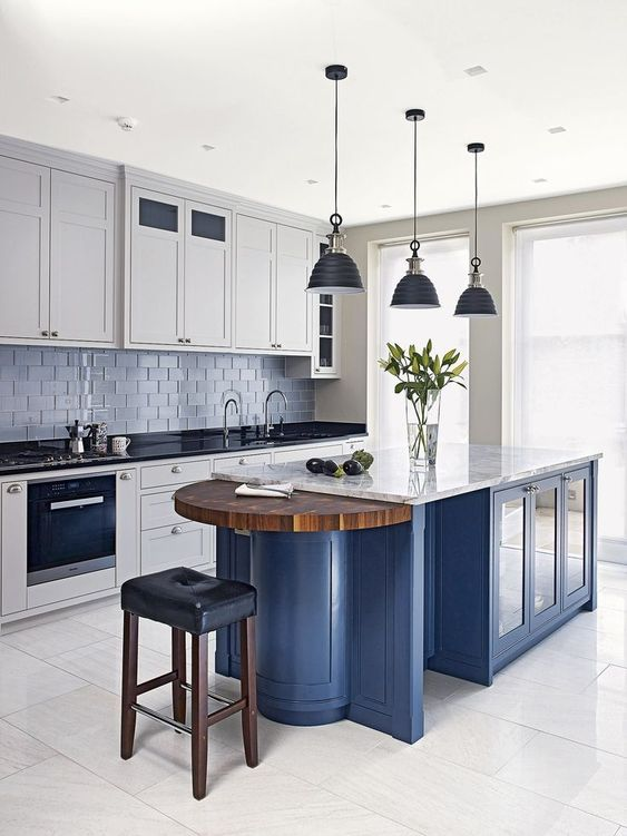 white cabinets with black countertops, a blue kitchen island with a white countertop and a wooden part seem very contrasting