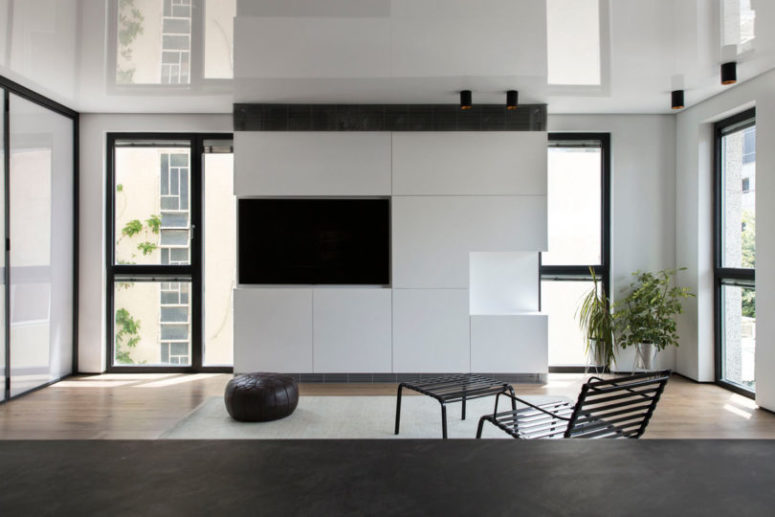 The living room is done with a sleek white TV cabinet and a built-in TV, a chair, a footrest and a leather ottoman
