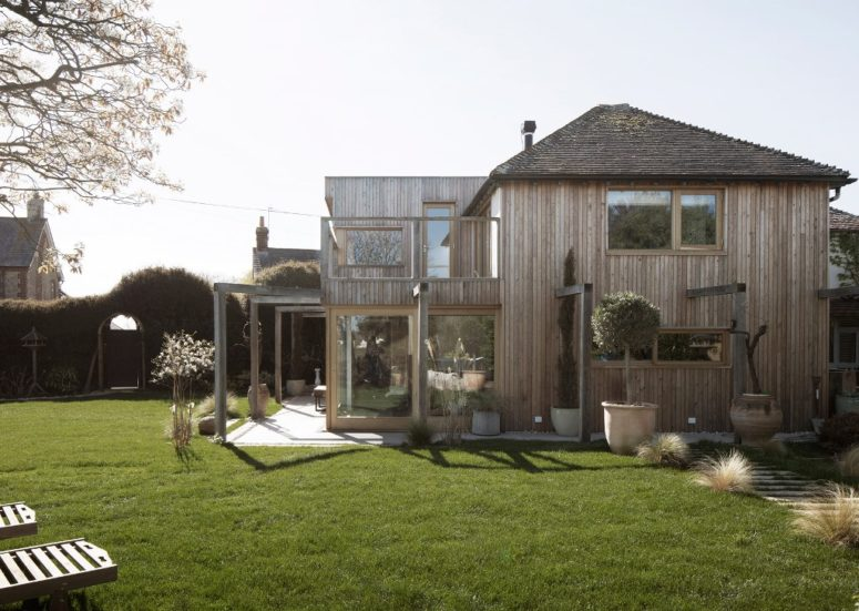 The outdoor space features a manicured lawn with potted greenery and blooms, loungers and a living fence