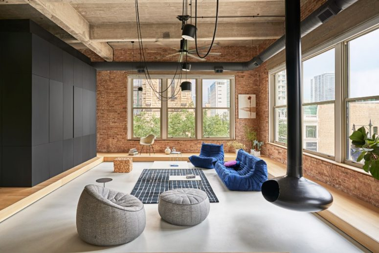 This is a living room zone done with bright contemproary furniture, a suspended fireplace and a black cube for storage and space division