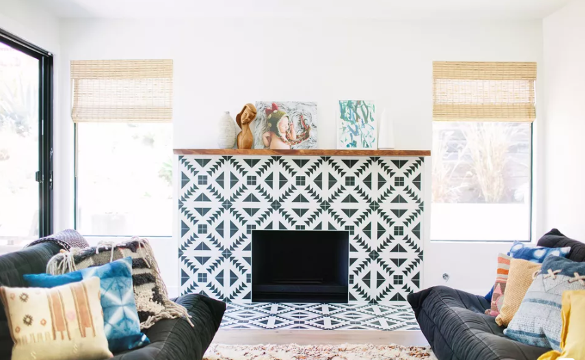 a modern fireplace clad with geometric black and white tiles that are extended to the floor for safety reasons
