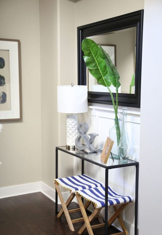 tropical leaves in a clear vase and striped nautical folding stools under the console add a slight beachy feel