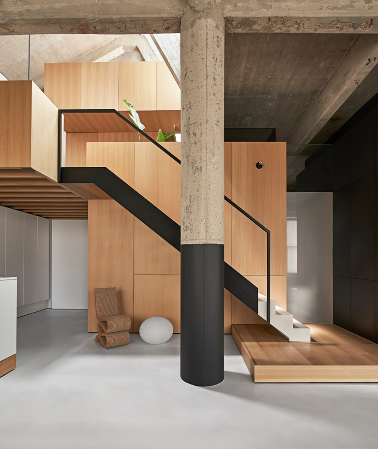There's a minimalist staircase and a wooden platform plus some catchy furniture