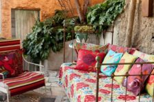 03 a shabby chic metal daybed with colorful blankets and pillows for a gypsy boho outdoor space