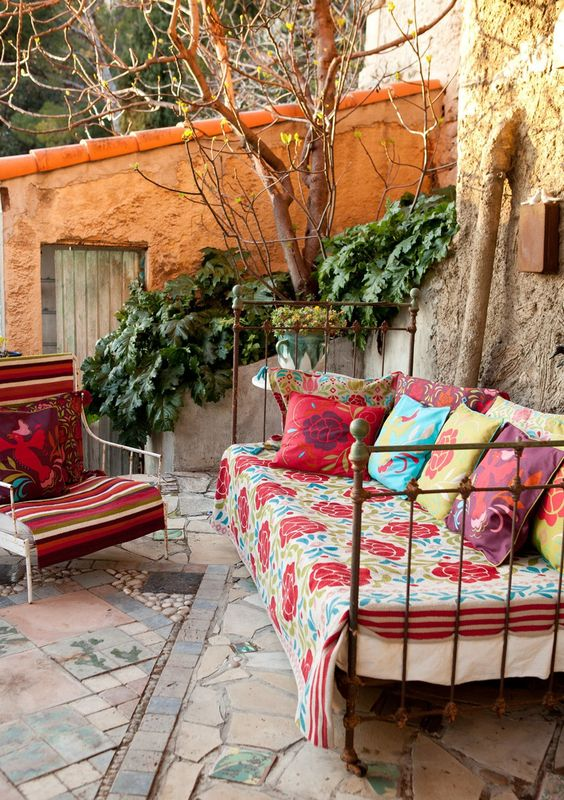 a shabby chic metal daybed with colorful blankets and pillows for a gypsy boho outdoor space