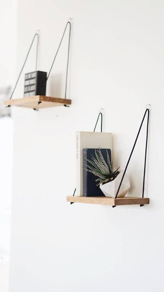simple and chic shelves with contrastign black threads and little rings on the walls for a modern or boho chic space