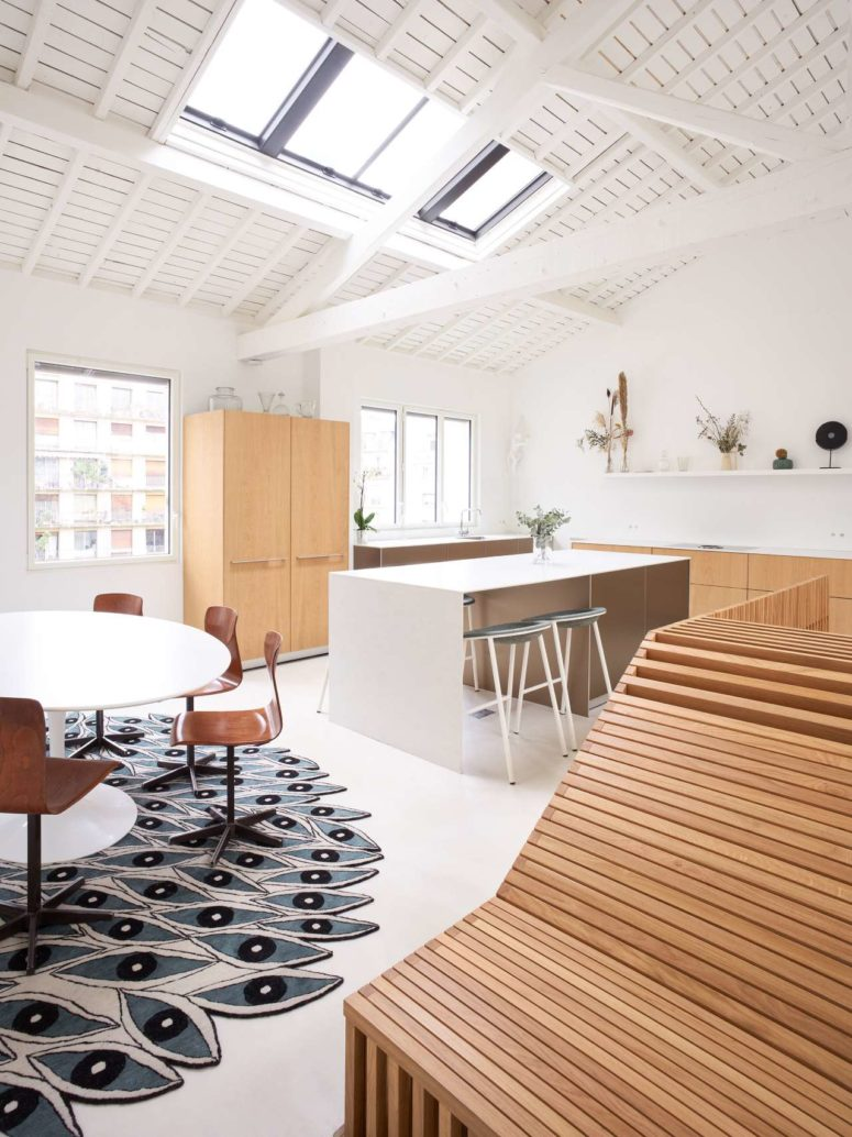 The kitchen features light-stained lower cabinets, a white kitchen island with a sitting space
