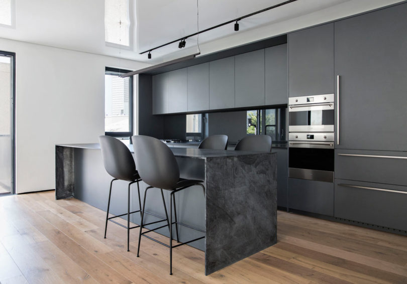 The kitchen is done with matte grey cabinets, a grey marble kitchen island, matte black chairs and a glass backsplash