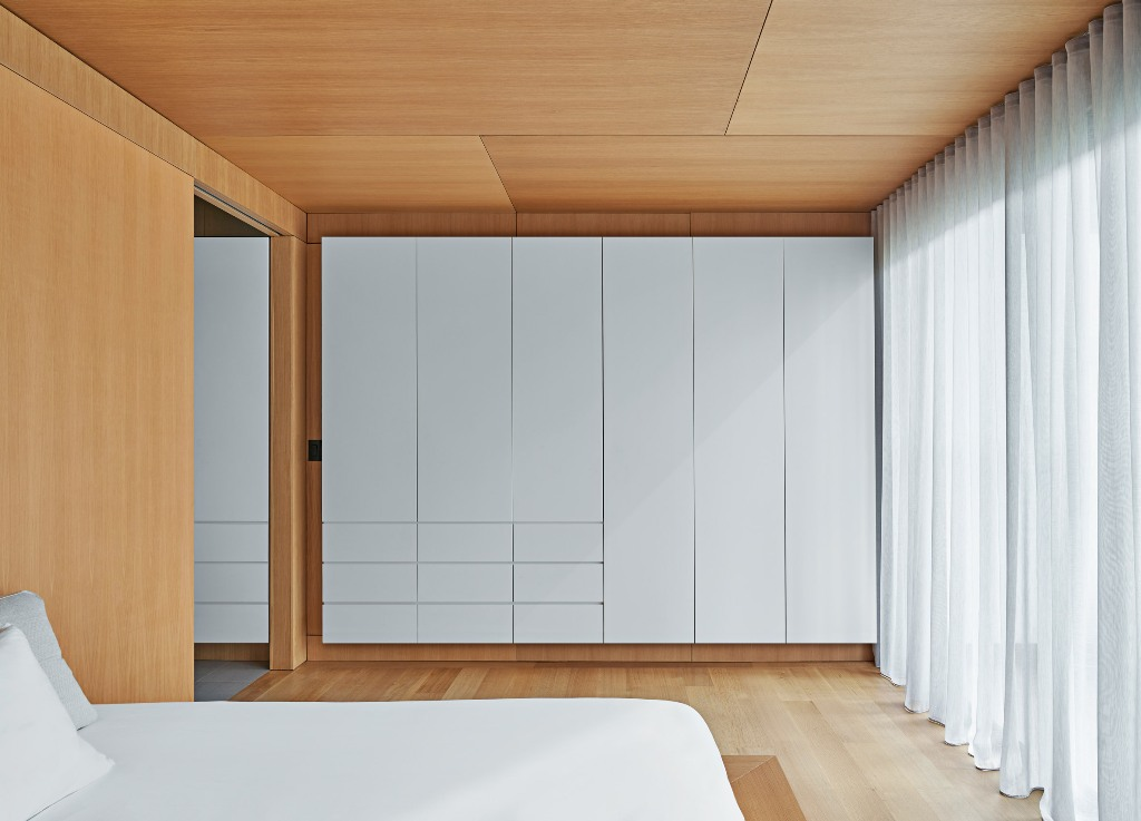 The master bedroom is super minimal and sleek   there's a bed and a large storage unit plus lots of light colored wood