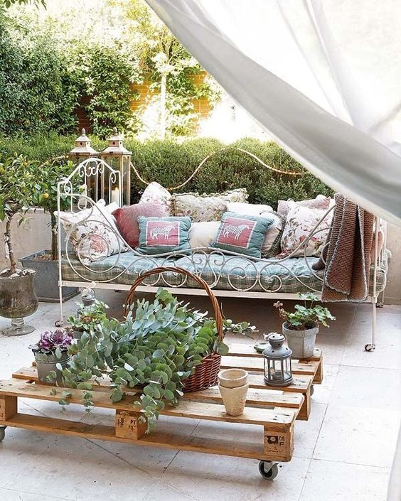 a super elegant and French chic forged daybed with lots of pillows on casters is a great piece for a romantic area
