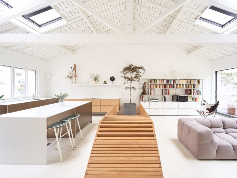 The spaces are divided in a smart way with a wooden slat staircase