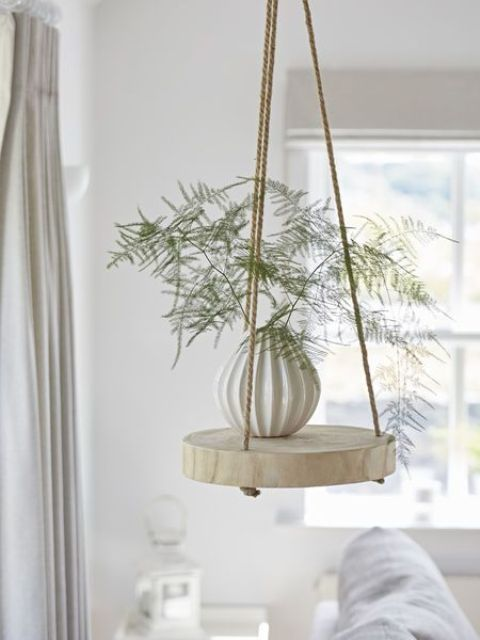 a cool and easy hanging shelf of a thick wood slice and ropes can be easily DIYed and will add a dreamy feel to the space