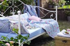 05 a vintage-inspired white forged daybed with many pillows and a floral blanket is timeless classics for an elegant garden