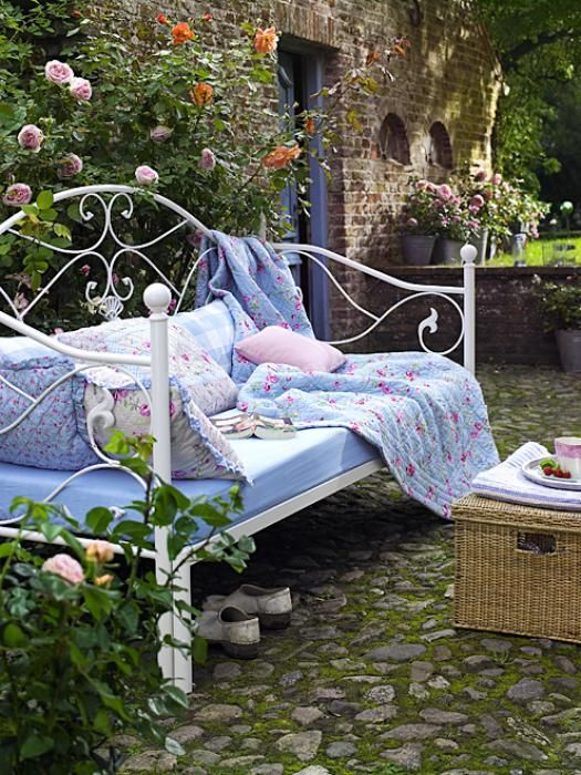 a vintage-inspired white forged daybed with many pillows and a floral blanket is timeless classics for an elegant garden