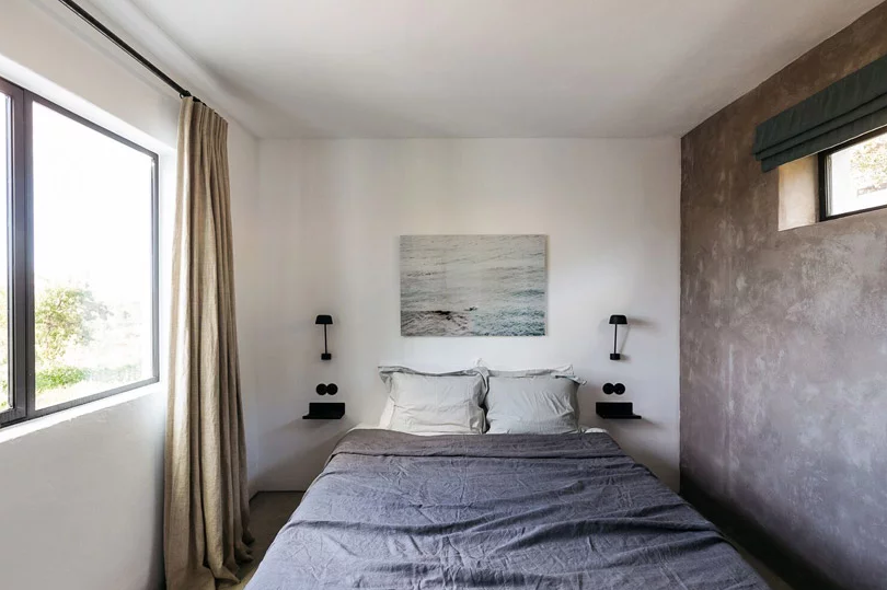 The bedroom is small yet peaceful, with a concrete wall, stylish bedding and an artwork