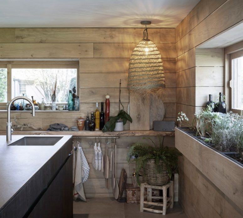 The kitchen is clad with light-colored wood, a wicker lamp, a basket planter and a metal kitchen island