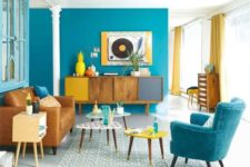 06 a colorful living room in bright blue, mustard and yellow brings the beauty of mid-century modern esthetics