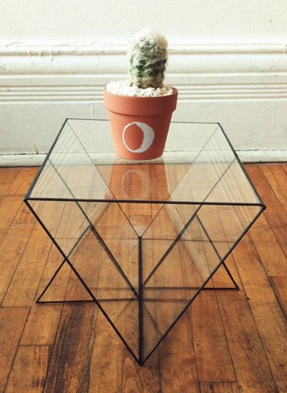 a glass geometric shaped table with black framing is a cool way to make a statement with its shape