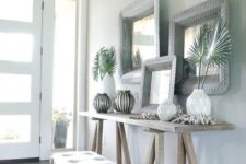 06 a neutral tropical entryway with light-colored wooden furniture, vases with tropical leaves, driftwood and mirrors in metal frames