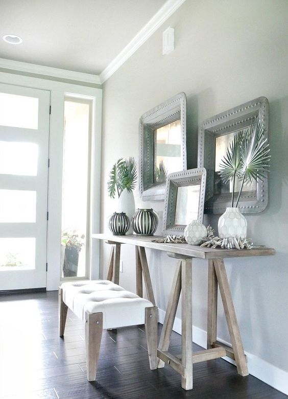 a neutral tropical entryway with light colored wooden furniture, vases with tropical leaves, driftwood and mirrors in metal frames