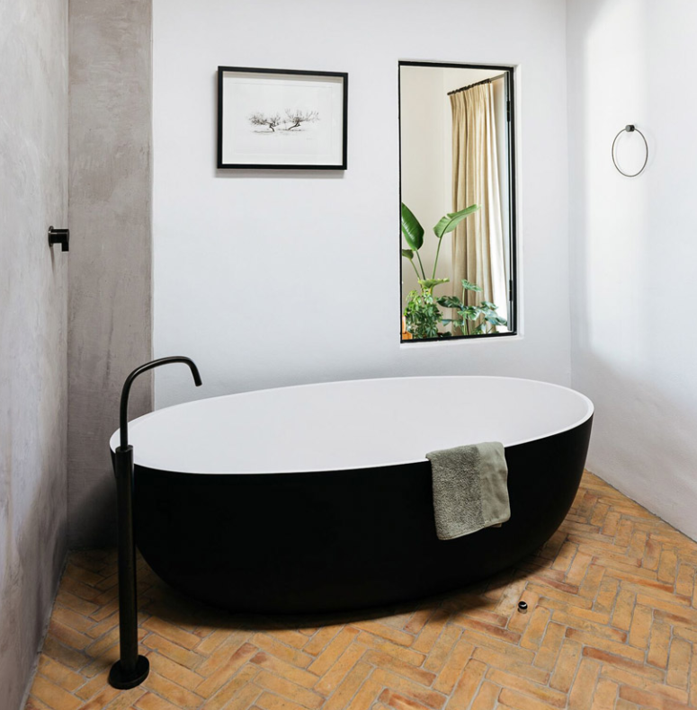 The bathroom is done with a black and white bathtub a black faucet and a large mirror