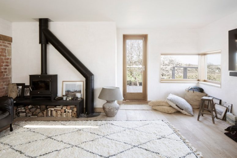The living room is a welcoming space, with a hearth, pillows, views and much natural light