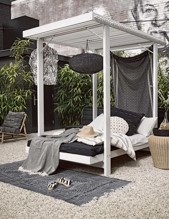 a cabana-style wooden daybed with a hanging blakc lamp, a curtain and lot sof pillows and blankets welcomes with its look