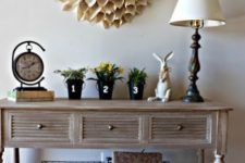 07 a farmhouse summer console table with a paper flower on the wlal, bright potted blooms and wire boxes