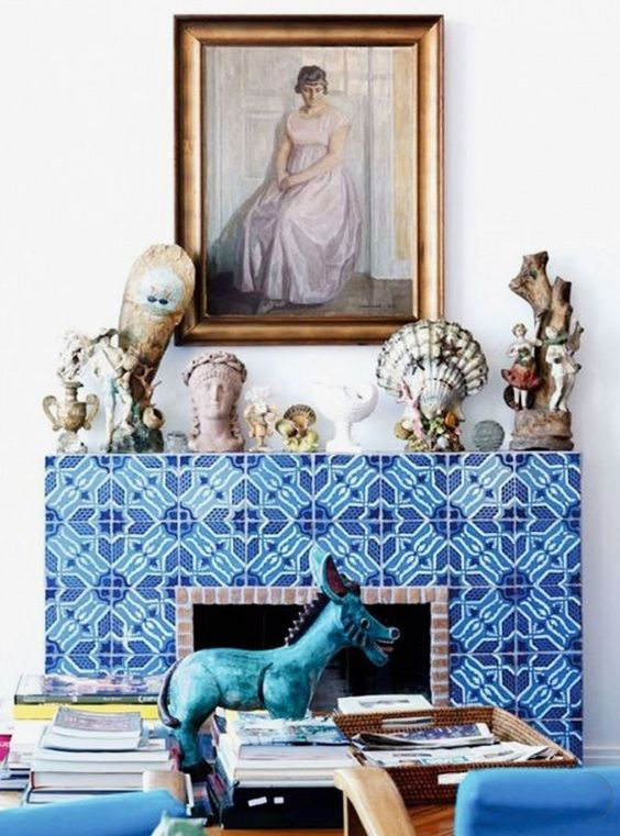 super bold blue and turquoise patterned tiles echoing blue chairs and a fun statuette create a unique look altogether
