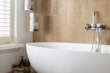 08 The bathroom is done with light colored wood and a modern oval tub