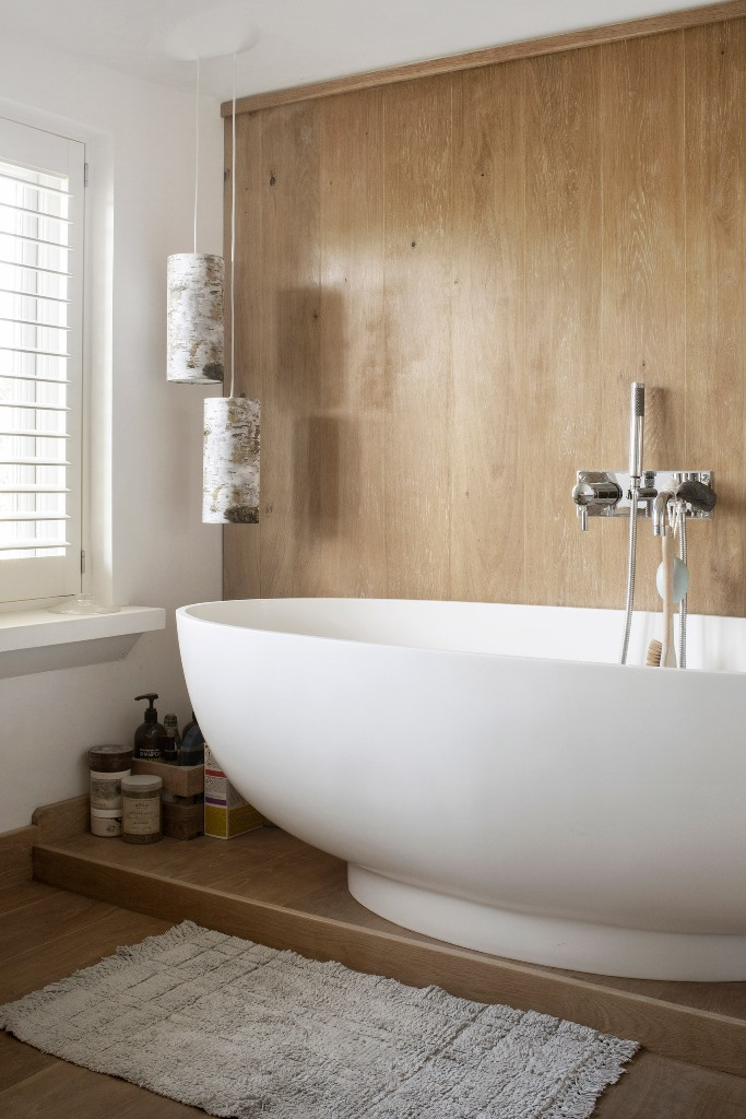 The bathroom is done with light colored wood and a modern oval tub