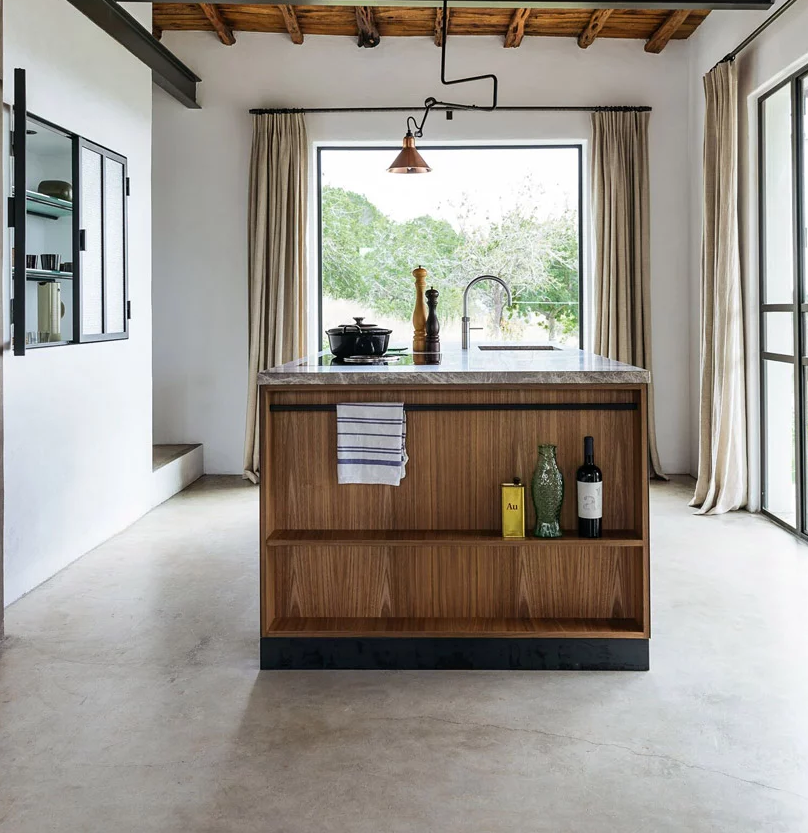 The kitchen features not only cabinets but also a stylish kitchen island with a stone countertop