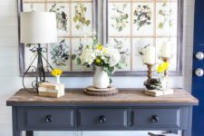 08 a farmhouse console table with greenery in crates and baskets and vintage botanical posters as artworks