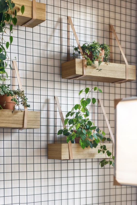hanging shelves of wood and leather like these ones can become your own rustic wall garden