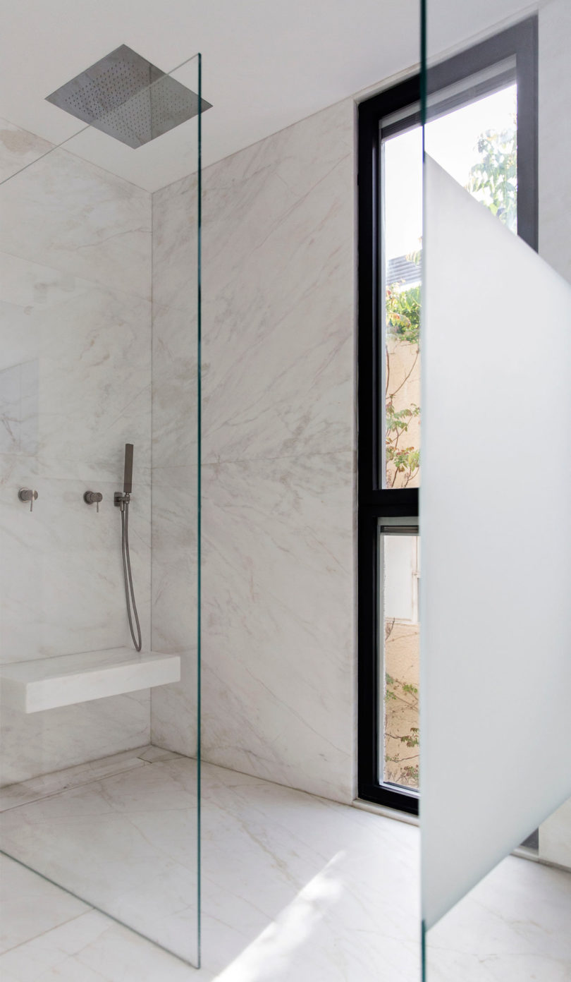 The bathroom is minimalist, done in white marble, with a seamless shower and a floor to ceiling window for a view and much light