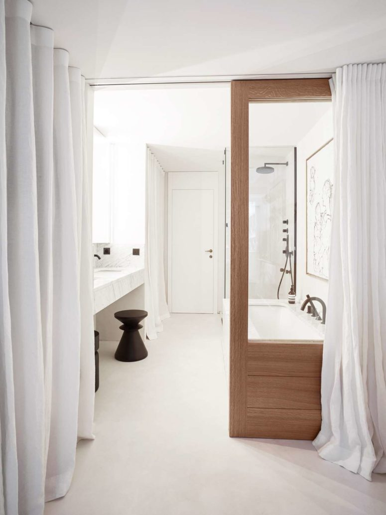 The bbathroom is also white, with a tub, a marble floating vanity, a wooden door and some curtains for privacy